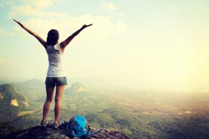 cheering hiking woman open arms on mountain peak