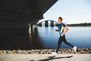 A DSLR photo of handsome muscular male athlete wearing tight emerald t-shirt, black tights (pantyhose) and white athletic shoes. He is alone this morning and running along the embankment near the river. He's running towards under the bridge with moderate pace.